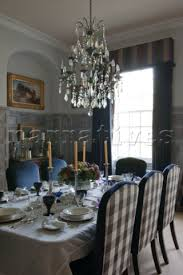 glass chandelier above dining table with gingham checked chairs in tiverton country home devon eng