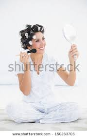 woman holding hand mirror. Cheerful Brunette In Hair Rollers Holding Hand Mirror And Applying Makeup At Home Bedroom Woman