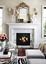 elegant living room features glass top coffee table across from light grey stools atop zebra cowhide rug placed in front of traditional fireplace adorned