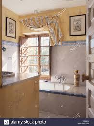 Blinde Gestreiften Stoff Drapiert über Fenster über Badewanne Im