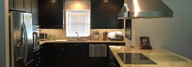 proper lighting and light granite countertops offset the dark dramatic cabinets in this kitchen remodel in santa fe generous and highly efficient storage