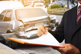 insurance adjuster examining a total loss vehicle