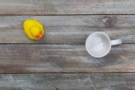 empty coffee mug yellow rubber duck on