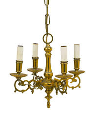 continental brass four light chandelier with baer stem and scrollwork arms fitted with candle cups