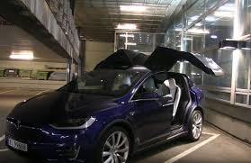 tesla model x falcon wing door opening in low ceiling parking garage video