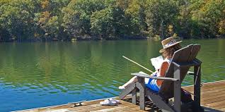 lake dock chairs. a guest reading in one of the adirondack style chairs available on our boat dock. lake dock