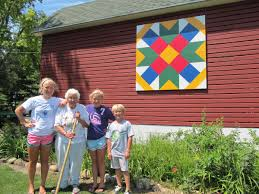 Outdoor Art Series: Southern Wisconsin Barn Quilts | WNIJ and WNIU & Nancy Nienhuis stands in front of her barn quilt
