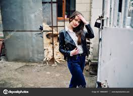 portrait of stylish young girl wear on leather jacket and ripped jeans at streets of city street fashion model style