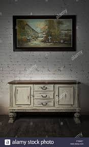 still life of vintage white sideboard and hanged framed painting on a dark wooden floor and white bricks wall in studio