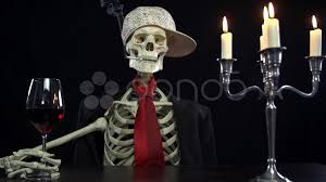 beautiful shot of skeleton sitting at the table with glass of wine and cigarette footage 37213748