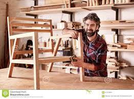 Artisan Designer Artisan Furniture Designer Sanding A Chair In His Workshop