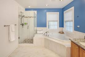 image of the light cream marble tile extends into the bathtub enclosure with brushed