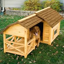 small wooden dog house a small deck portion allows the dog to lay outside of the