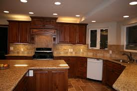 cherry cabinets with granite countertops and backsplash