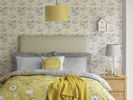 yellow themed bedroom with grey patterned wallpaper and yellow soft furnishings