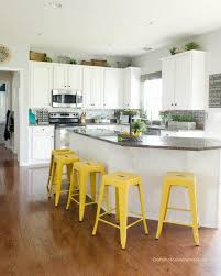 bright white kitchen painted with chalk paint yellow stools dark counter tops wood floors