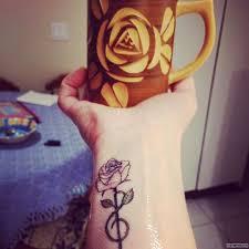 скрипичный ключ в виде розы тату на запястье у девушки добавлено