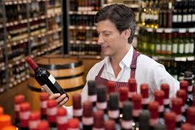 sales clerk holding wine bottle in shop sales clerk jobs