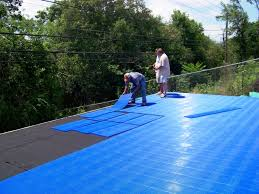 two men laying sport court tiles in backyard basketball installation