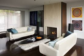 living room couches facing each other. living spaces couches hardwood floors tile fireplace surround wall decorations window led lights rug table room facing each other
