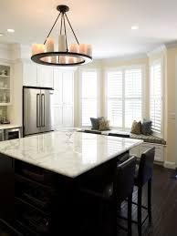 round kitchen chandelier with pillar candles over white kitchen island by fiorella design