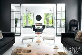 vintage lucite ribbon chandelier black and white veneered cabinets continue the spaces seamless movement finished with a grouping of four brass stools