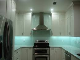 extra tall white kitchen cabinet with blue aqua glass tiles backsplash and stainless steel range hood above freestanding range