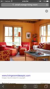 This living room has a warm color scheme because of its use of red, orange  and yellow. The red-orange walls and the bright red chairs create a large  bubbly ...