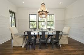chic dining room features pottery barn wood bead chandelier over restoration hardware salvaged wood weathered concrete x base table lined by tolix chairs