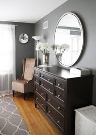 grey walls with brown furniture. gray with dark furniture round mirror over long dresser both grey walls brown
