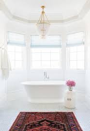 window filled with a roll top tub and a gooseneck tub filler and a white garden stool illuminated by a white beaded chandelier aerin jacqueline white