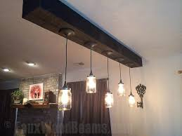 vintage style bell jar lights hung from a heavy sandblasted ceiling beam