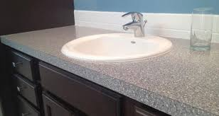 there are lot s of fantastic prefab bathroom vanities that use plastic laminate counters you can have one custom made by your contractor too