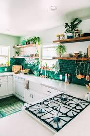 emerald rectangular tile backsplash white kitchen cabinets white countertops wooden floating shelves potted plants plates cups napkins