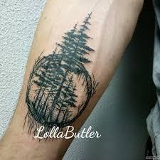 лес в виде деревьев в круге тату на предплечье у парня добавлено