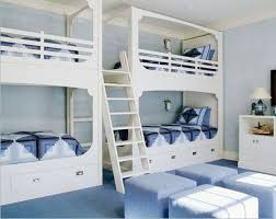 two sets of white bunk beds with one ladder in a blue room