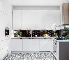 A glossy black tile backsplash pliments the sleek white