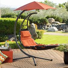 black metal hanging swing chair with orange seat completed by umbrella on mocha rug outdoor outside