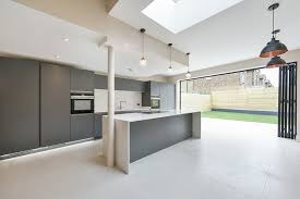 large bifold doors connect this large modern kitchen with light grey porcelain floor tiles to the