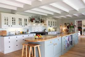 large kitchen islands with seating and storage stools cabinets drawers  chopping board shelf flowers clock farmhouse