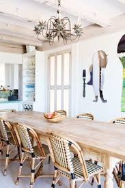 a nickey kehoe farm table surrounded by french rattan bistro chairs defines the dining room