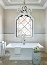 chandelier bathroom lighting. luxurious french bathroom features a crystal chandelier hung from tray ceiling over freestanding lighting