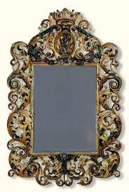 An Austrian or South German carved giltwood and polychrome decorated mirror,  possibly Innsbruck, circa 1700 the rectangular plate within a moulded frame,