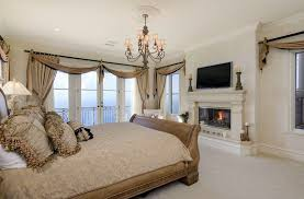traditional master bedroom with fireplace ocean views and balcony
