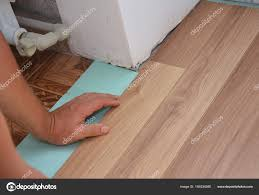 installing laminate flooring. Man Installing Laminate Wood Flooring In Problem Area. Worker Wooden Flooring. Handyman A