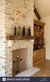 hard wood floor stone fireplace built in cabinets and statuary in a living room california luxury home