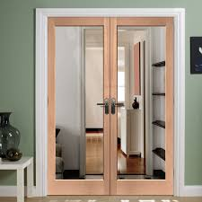 spacious interior double doors with glass and green wall paint also laminated wooden flooring idea