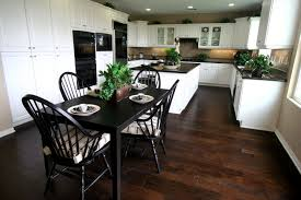 This Sprawling Kitchen Sets Pristine White Cabinetry Over Rich, Warm Toned  Hardwood Flooring, While