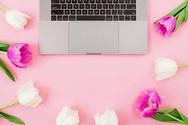laptop with tulips flowers on pink background flat lay top view position with