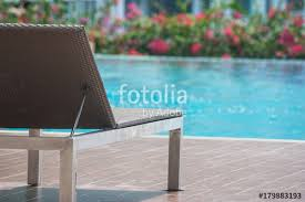 close up daybed setting on wooden floor beside swimming pool at outside the resort selective focus